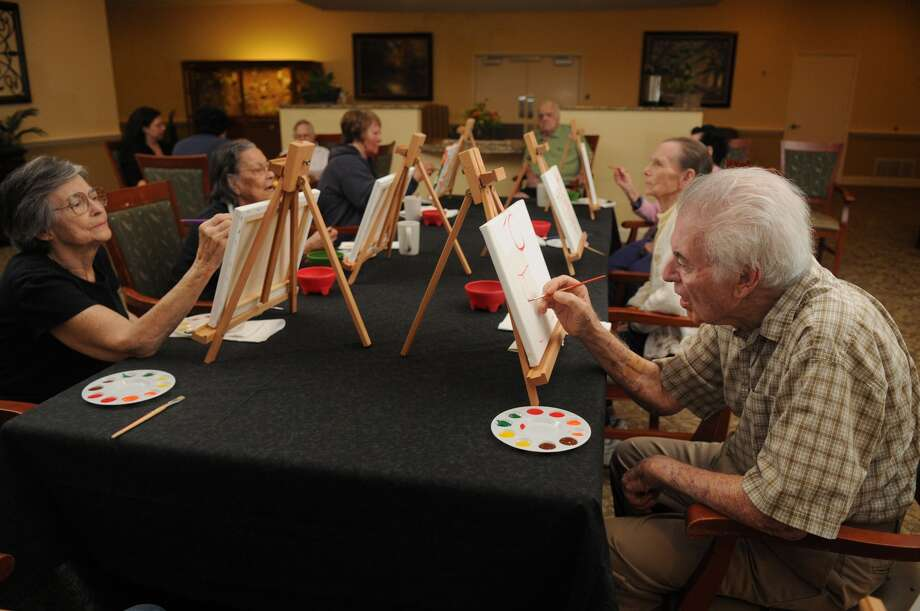 Charles Perricone, right, and other residents at Silverado Cypresswood Memory Care Community work on pieces during a class in advance of the Wine and Watercolors Mixer and Silent Auction. Photo: Jerry Baker, Freelance