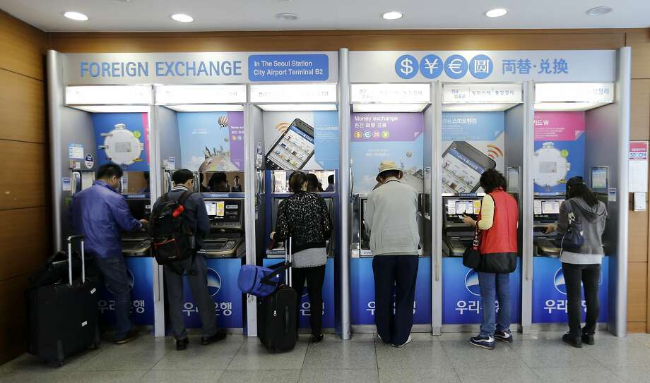 In this Thursday, Oct. 9, 2014 photo, depositors use automated teller machines at Seoul Railway Station in Seoul, South Korea. After an avalanche of data breaches, South Korea's national identity card system has been raided so thoroughly by thieves that the government says it might have to issue new ID numbers to every citizen over 17 at a possible cost of billions of dollars. Photo: Ahn Young-joon, Associated Press