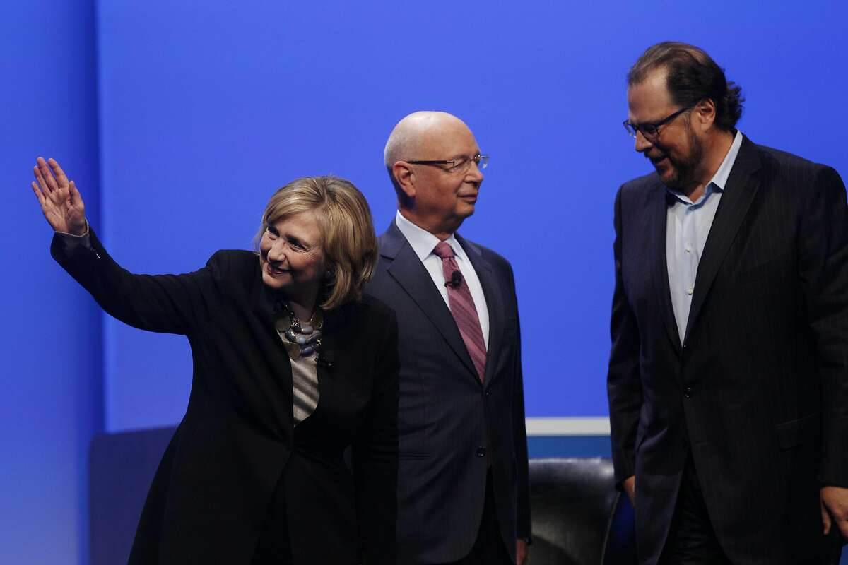 Former Secretary of State Hillary Rodham Clinton (l to r) waves to the audience after a Question and Answer Session with Klaus Schwab, executive chairman of the World Economic Forum, who talks with Marc Benioff, chairman and CEO salesforce.com, after a keynote in Moscone South at Salesforce's Dreamforce conference on Tuesday, October 14, 2014 in San Francisco, Calif.