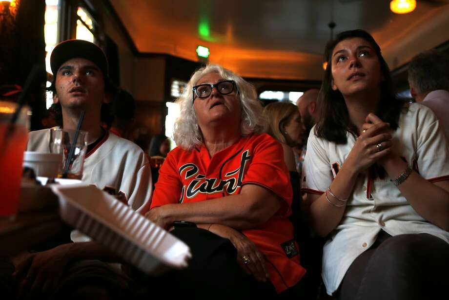 As the Giants play a wild card playoff game in Pittsburgh, Surma Mauro (center) and her children Raphael (left) and Saskia (right) nervously watch the action on television at the Dogpatch Saloon on 3rd Street.
