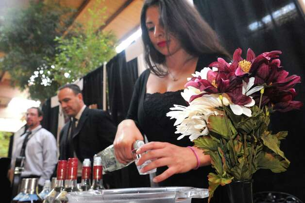 Nicole De La Cruz of Empire Merchants pour a sample of Jose Cuervo Cinge during The New York State Liquor Store Association 2014 Annual Holiday Trade show at The Desmond on Tuesday Oct. 14, 2014 in Colonie, N.Y.  (Michael P. Farrell/Times Union) Photo: Michael P. Farrell / 10029027A
