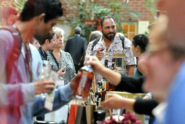 Tom Vasquez of Cairo, center, samples a wine from Opici importers and suppliers during The New York State Liquor Store Association 2014 Annual Holiday Trade show at The Desmond on Tuesday Oct. 14, 2014 in Colonie, N.Y.  (Michael P. Farrell/Times Union) Photo: Michael P. Farrell / 10029027A