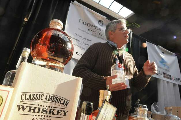 Eugene V. Marra, right, owner of Copperstown Distillery displays and samples his spirts during The New York State Liquor Store Association 2014 Annual Holiday Trade show at The Desmond on Tuesday Oct. 14, 2014 in Colonie, N.Y.  (Michael P. Farrell/Times Union) Photo: Michael P. Farrell / 10029027A