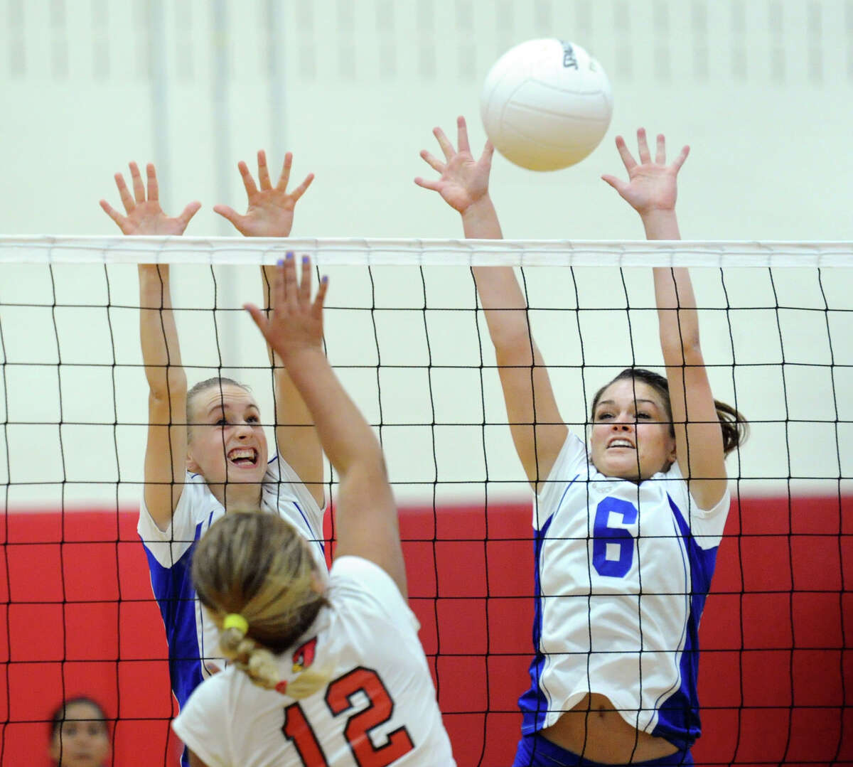 At left, Emily Milukas (#4) of Darien and teammate, Sami Huff (#6), right, block the spike of Jahaira Guerra (#12) of Greenwich, at bottom during the girls high school volleyball between Greenwich High School and Darien High School at Greenwich, Tuesday, Oct. 14, 2014. Darien won the match over Greenwich, 3-0.