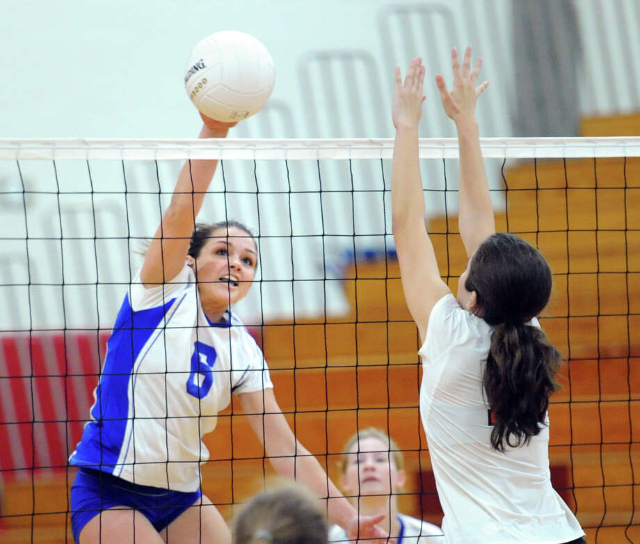 At left, Sami Huff (#6) of Darien scores a point on a spike during the girls high school volleyball between Greenwich High School and Darien High School at Greenwich, Tuesday, Oct. 14, 2014. Darien won the match over Greenwich, 3-0. Photo: Bob Luckey / Greenwich Time