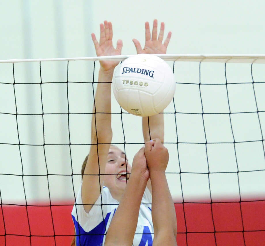 At top, Emily Milukas (#4) of Darien blocks a Greenwich spike during the girls high school volleyball between Greenwich High School and Darien High School at Greenwich, Tuesday, Oct. 14, 2014. Darien won the match over Greenwich, 3-0. Photo: Bob Luckey / Greenwich Time