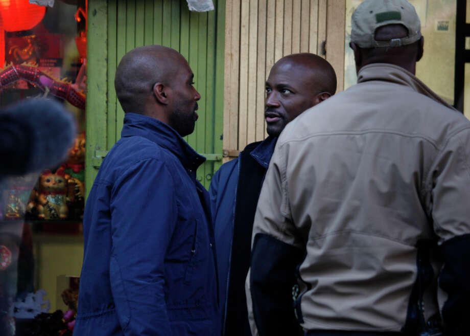"Actor Taye Diggs, right, talks with Horace Knight, left, stunt double for Digg's character Terrance English, between shots on the set of TNT's ""Murder in the First"" while shooting a scene in San Francisco's Chinatown district. Photo: Lea Suzuki / The Chronicle / ONLINE_YES"