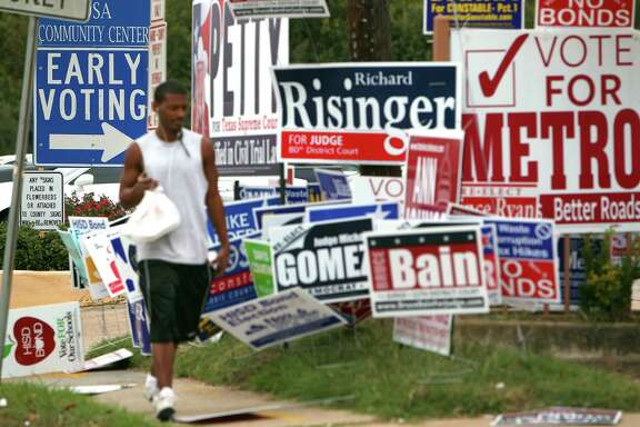 His lunch in hand, Zachary Brown walks past a group of campaign signs littering the area outside early voting at the Harris County Precinct 3 Trini Mendenhall Sosa Community Center Friday, Oct. 26, 2012, in Houston.  ( Johnny Hanson / Houston Chronicle )