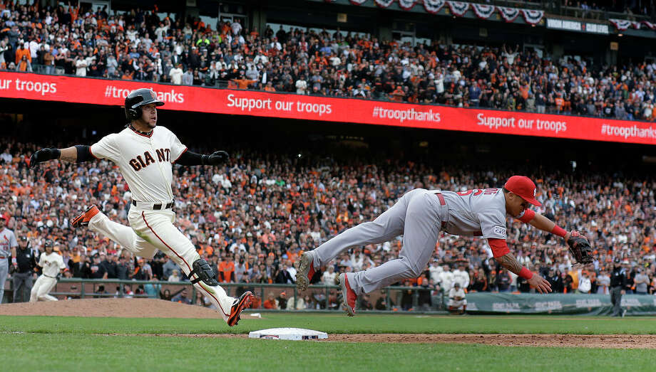 San Francisco Giants' Gregor Blanco is safe at first as St. Louis Cardinals second baseman Kolten Wong fails to catch the throw during the 10th inning of Game 3 of the National League baseball championship series against the St. Louis Cardinals Tuesday, Oct. 14, 2014, in San Francisco. Photo: David J. Phillip, Wire Photo / AP