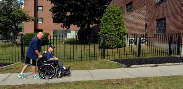 Ned Norton pushes one of the members of the Warriors on Wheels program to his gym on Green Street Wednesday morning, Oct. 8, 2014, in Albany, N.Y.   (Skip Dickstein/Times Union) Photo: SKIP DICKSTEIN / 10028942A