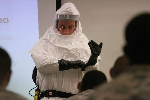 Cpl. Zachary Wicker shows how to put gloves on while in germ-protective gear in Fort Bliss, Texas, Tuesday, October 14,  2014. About 500 Fort Bliss soldiers are preparing for deployment to West Africa where they will provide support in a military effort to contain the Ebola outbreak. (AP Photo/Juan Carlos Llorca) Photo: Juan Carlos LLorca, Associated Press / AP
