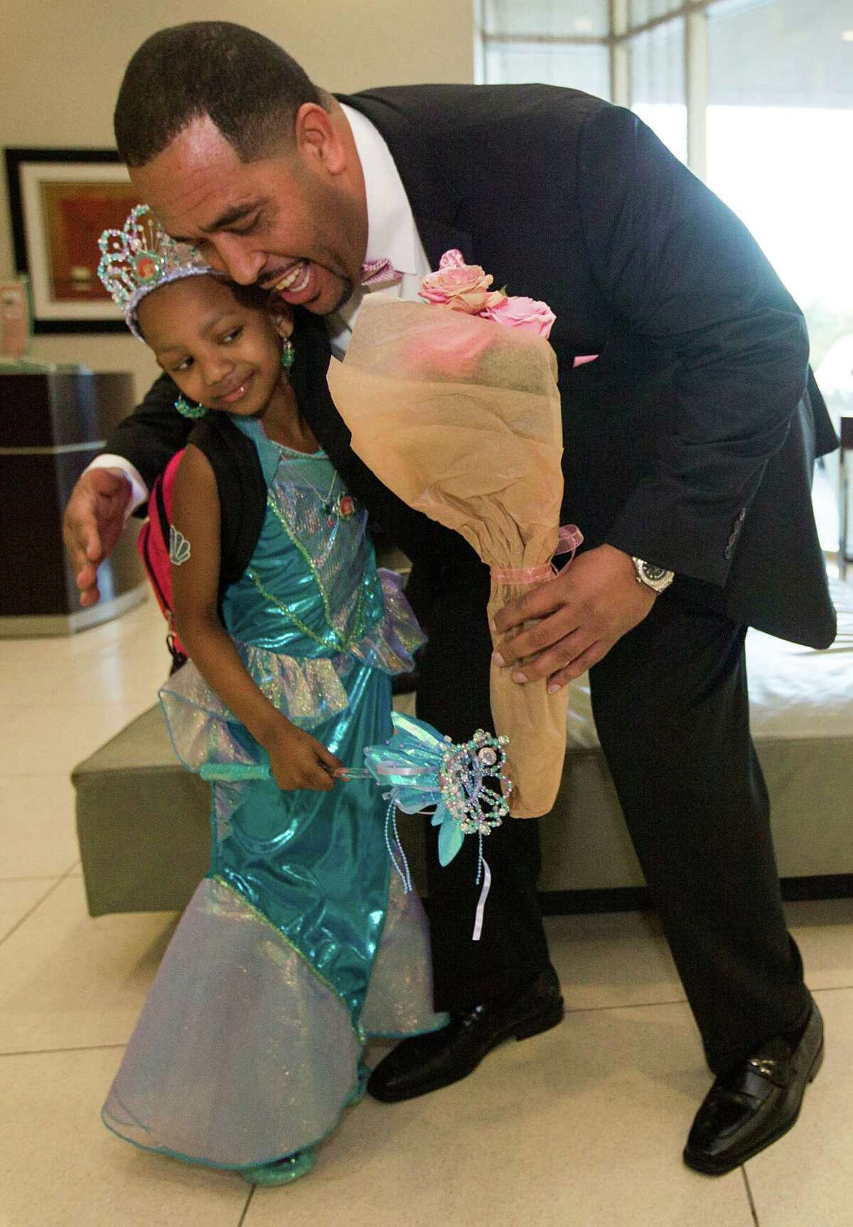 Kyssi Andrews is embraced by personal trainer Troy Cousin as he picks her up for her 6th birthday dinner on Tuesday, Oct. 14, 2014, in Houston.
