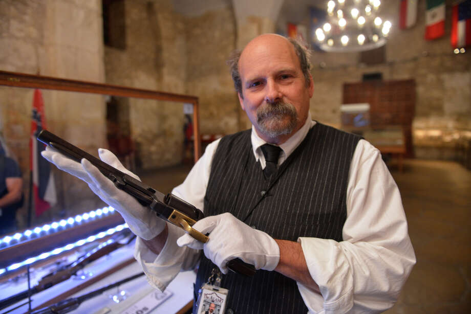 "Alamo Historian and Curator Dr. Bruce Winders displays the ""Firearms of the Texas Frontier, Flintlocks to Cartridge (1836-1876) which will be on display in the Alamo Shrine through April 15, 2015. He is holding a Colt Walker pistol. Photo: Robin Jerstad"