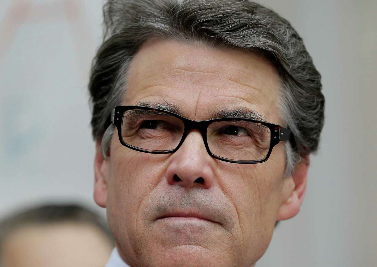 FILE - In this Aug. 19, 2014 file photo, Texas Gov. Rick Perry talks to the media and supporters after he was booked at the Blackwell Thurman Criminal Justice Center, in Austin, Texas. Perry will make his first court appearance on Halloween as his defense team tries to quash the two felony counts of abuse of power against him on both constitutional and technical grounds. (AP Photo/Eric Gay, File)