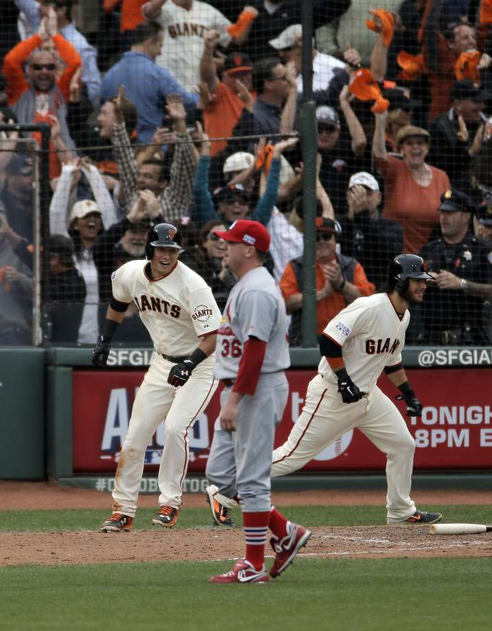 Joe Panik (12) and Brandon Crawford (35) run to join the rest of the team as pitcher Randy Choate (36) walks by after his errant throw allowed Crawford to score in the bottom of the tenth inning as the Giants defeated the St. Louis Cardinals 5-4 in Game 3 of the NLCS at AT&T Park in San Francisco, Calif., on Tuesday, October 14, 2014. Photo: Carlos Avila Gonzalez, The Chronicle