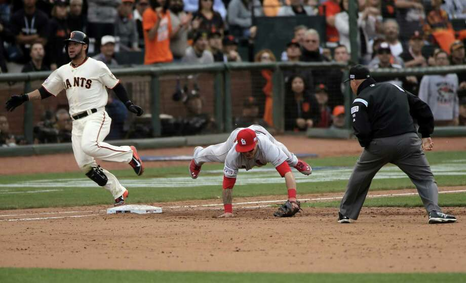 Gregor Blanco crosses first base as the Cardinals' Kolten Wong dives in vain for Randy Choate's wild throw, which allowed the winning run to score. Photo: Carlos Avila Gonzalez / The Chronicle / ONLINE_YES