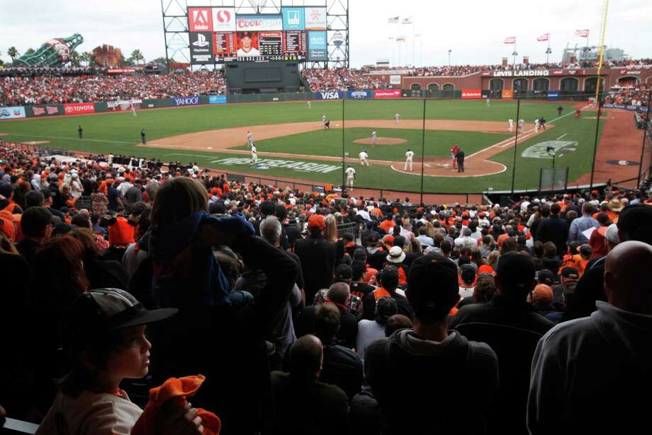 Brown Schneider, 8, left, watches the bottom of the 10th inning during NLCS Game 3 against the Cardinals October 14, 2014 at the AT&T Park stadium in San Francisco, Calif. The Giants won in the 10th inning. Photo: Leah Millis / The San Francisco Chronicle / ONLINE_YES