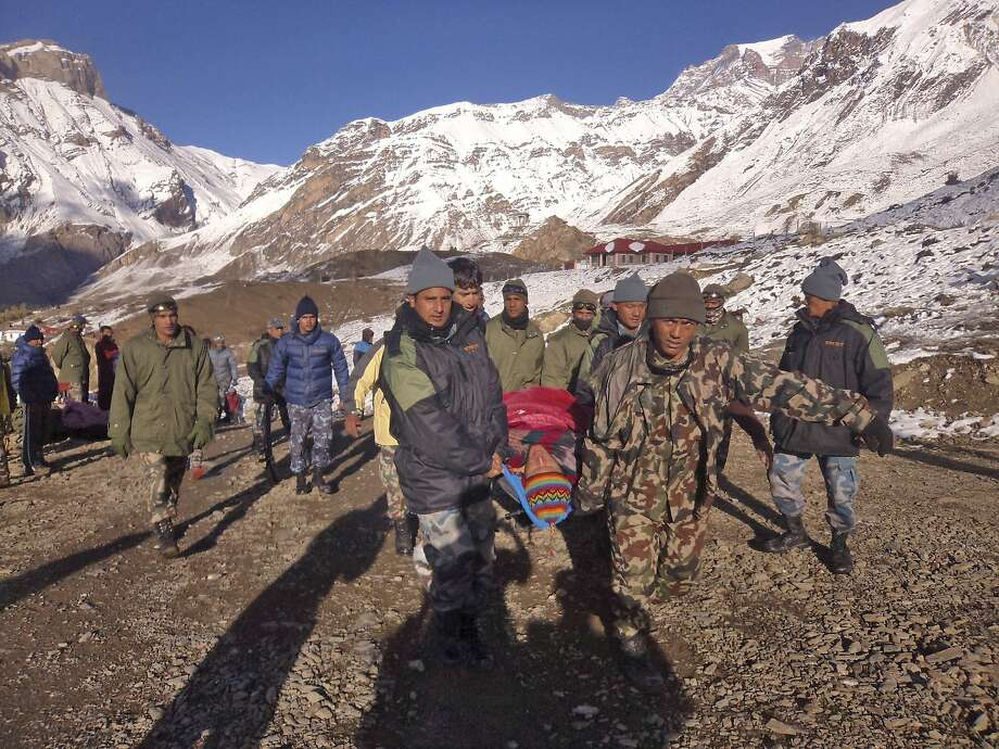 In this photo provided by the Nepalese army, soldiers carry an avalanche victim before he is airlifted in Thorong La pass area, Nepal, Wednesday, Oct. 15, 2014. An avalanche and blizzard in Nepal's mountainous north have killed at least 12 people, including eight foreign trekkers, officials said Wednesday. Five other climbers were hit by a separate avalanche on Mount Dhaulagiri and remain missing. (AP Photo/Nepalese Army) Photo: Associated Press