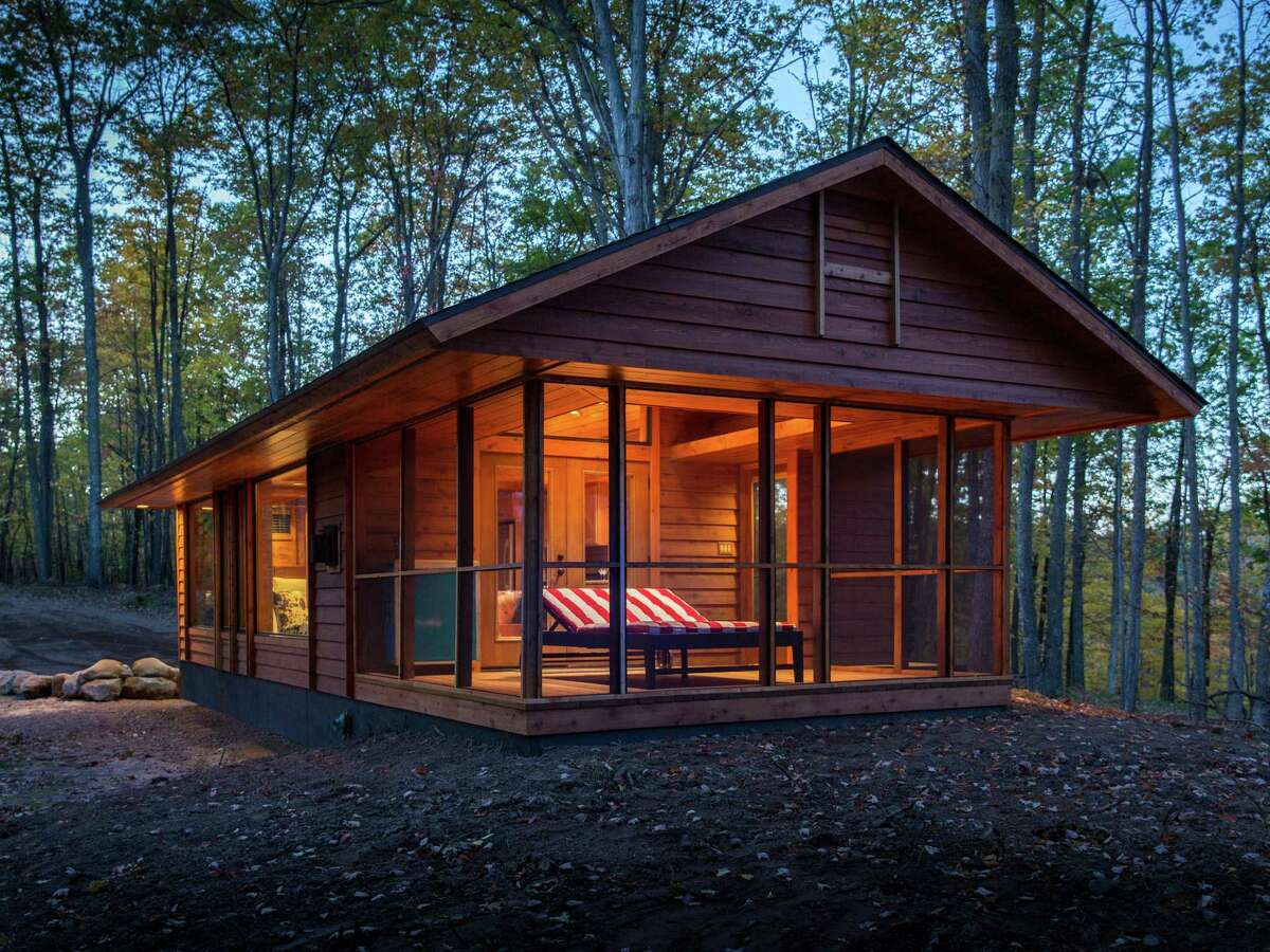 Well-Appointed Cottage Inspired by and built by the team responsible for the gorgeous cottages at the Canoe Bay resort in the woods of Wisconsin, the 392-square-foot Escape looks like a high-end cabin but is actually a 28- by 14-foot Park Model RV on wheels. Vaulted ceilings and a large window wall give an airy feel to the cottage, which includes a living room with fireplace and kitchen wall and a separate bedroom and bath. Large French doors open to a screened porch that can be used as an extended living room, sleeping porch, or a dining area. The red-striped chaise lounge doubles as a bed with heated coils, perfect for naps on chilly days. Escape is available to rent at Canoe Bay, or can be custom-built for buyers and delivered ready to live-in. Prices start at $79,900. Look inside the Escape. Read: The 23 best movie homes