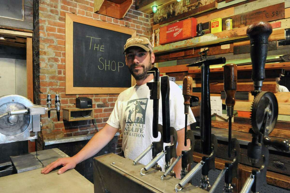 Kevin Blodgett in his new bar called The Shop on Friday, Oct. 10, 2014, in Troy, N.Y. A 35,000-square-foot Troy building that was home to the former Trojan Hardware for more than 90 years will soon have three street-level spaces devoted to food and drink. The building, on the corner of Fourth and Congress streets, was redeveloped over the past nine years by owner Kevin Blodgett, who did the renovations himself and is opening two of the businesses, a restaurant-bar called The Shop and a deli called Harrison's Corner Market. (Michael P. Farrell/Times Union)