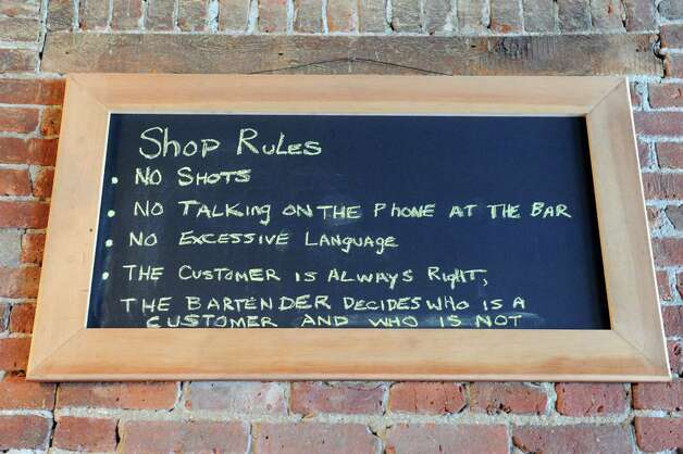 A list of house rules at Kevin Blodgett's new bar called The Shop on Friday Oct. 10, 2014 in Troy, N.Y. A 35,000-square-foot Troy building that was home to the former Trojan Hardware for more than 90 years will soon have three street-level spaces devoted to food and drink. The building, on the corner of Fourth and Congress streets, was redeveloped over the past nine years by owner Kevin Blodgett, who did the renovations himself and is opening two of the businesses, a restaurant-bar called The Shop and a deli called Harrisona€™s Corner Market. (Michael P. Farrell/Times Union) Photo: Michael P. Farrell / 10028962A