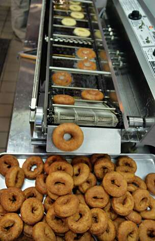 Doughnuts roll off the doughnut robot at Cider Belly Doughnuts on North Pearl Street Thursday Oct. 9, 2014, in Albany, NY.  (John Carl D'Annibale / Times Union) Photo: John Carl D'Annibale / 10028944A