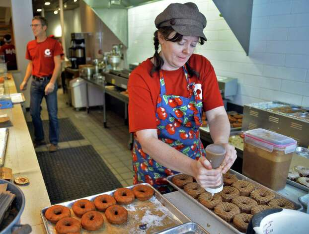 Co owner Jennifer Novak maples doughnuts at Cider Belly Doughnuts shop on North Pearl Street Thursday Oct. 9, 2014, in Albany, NY.  (John Carl D'Annibale / Times Union) Photo: John Carl D'Annibale / 10028944A