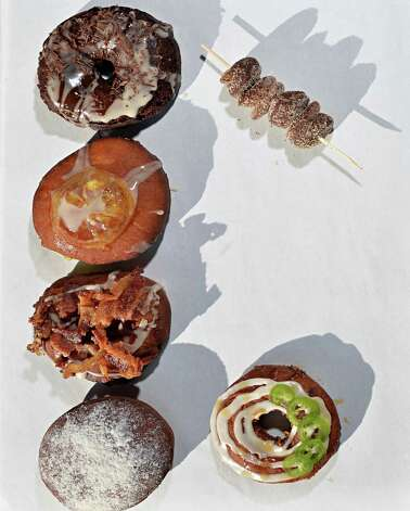 Doughnuts (clockwise from top left) chocolate nibbles, Jalape–o cheddar, blackberry cassis, maple bacon, local lemon and dark chocolate sea salt at Nibble, Inc. on Broadway Thursday Oct. 2014, in Troy, NY.  (John Carl D'Annibale / Times Union) Photo: John Carl D'Annibale / 10028960A
