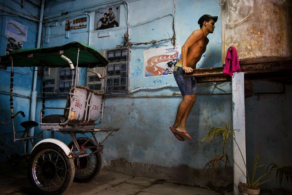 ANYWHERE CAN BE A GYM: A young man does chest dips using the beams that hold a water tank at his house in Havana.