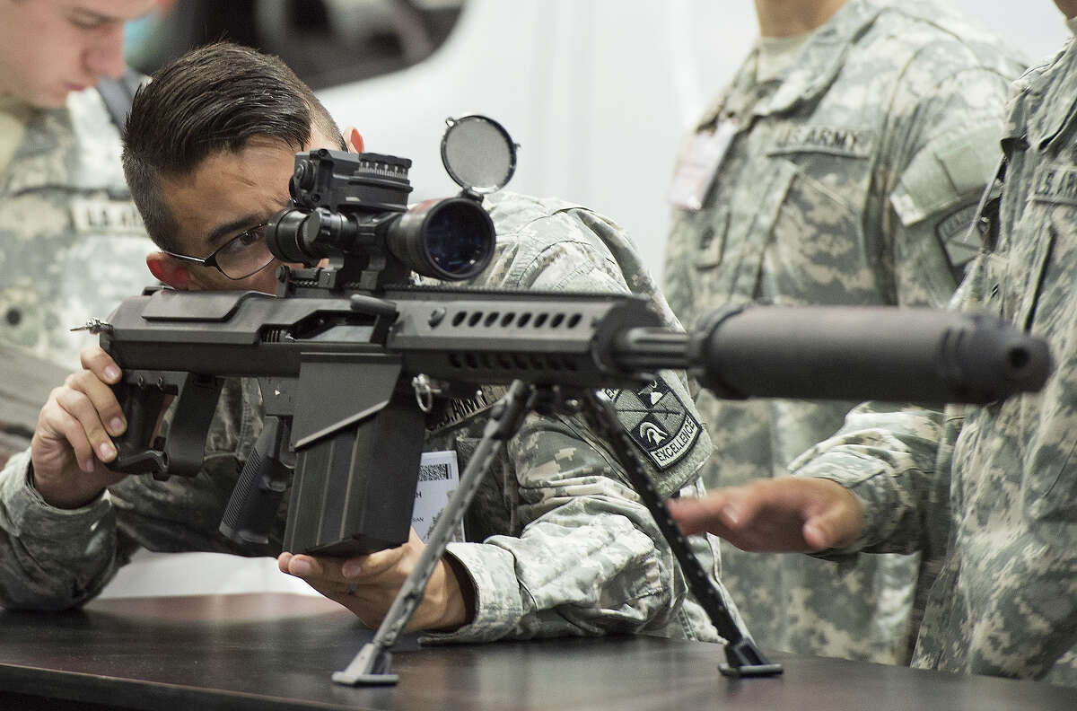 A US Army soldier looks over a Barrett M107A1 rifle, which is designed to be used with a suppressor, during the Association of the United States Army Annual Meeting and Exposition in Washington, DC, October 13, 2014. Headquartered in Murfreesboro, Tennessee, Barrett is a large-caliber rifle design and manufacturing company.