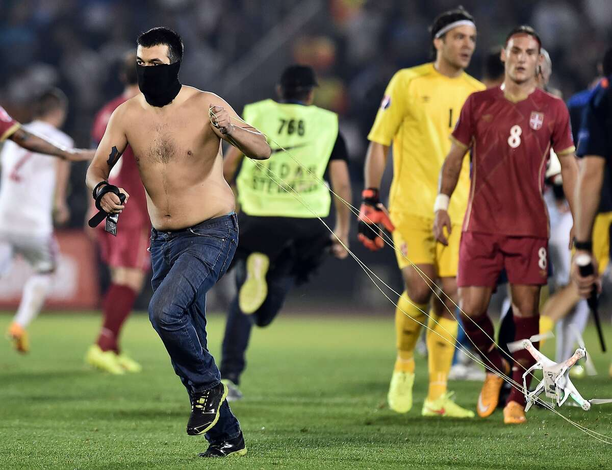 DRONE FLY-OVER TRIGGERS SOCCER MELEE: A masked Serbian supporter drags a drone that had been carrying a banner promoting