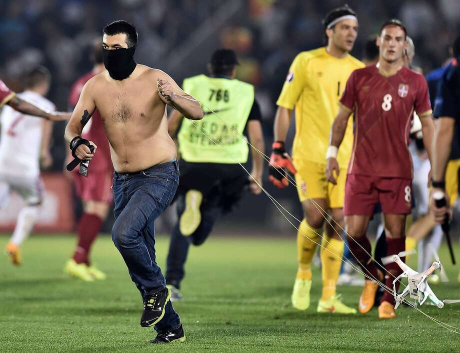 """DRONE FLY-OVER TRIGGERS SOCCER MELEE: A masked Serbian supporter drags a drone that had   been carrying a banner promoting """"greater Albania"""" over the pitch of a soccer match between   Serbia and Albania in Belgrade. When Serbian player Stefan Mitrovic grabbed the low-flying   flag and pulled down the drone, a brawl broke out among the players. Referees called off the   match. Photo: Andrej Isakovic, AFP/Getty Images"""