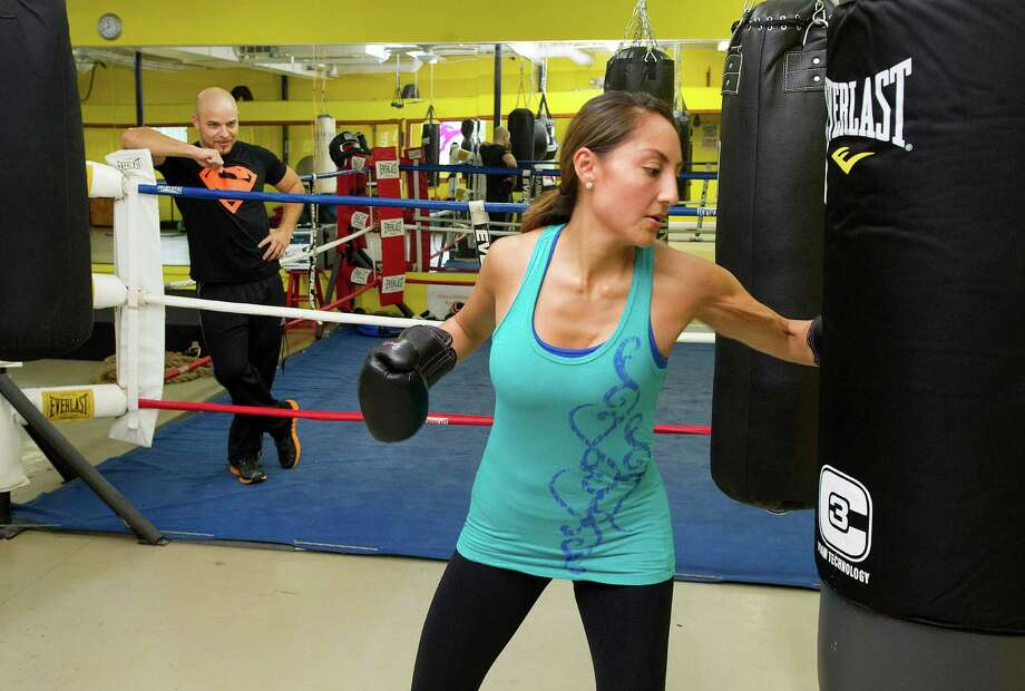 Maribel Sandalo gets encouragement from her husband, gym owner Paul Sandalo, as she works out at Heavy Hitting Boxing and Fitness in Stamford, Conn., on Wednesday, October 15, 2014. Photo: Lindsay Perry / Stamford Advocate