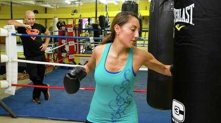 Maribel Sandalo gets encouragement from her husband, gym owner Paul Sandalo, as she works out at Heavy Hitting Boxing and Fitness in Stamford, Conn., on Wednesday, October 15, 2014.