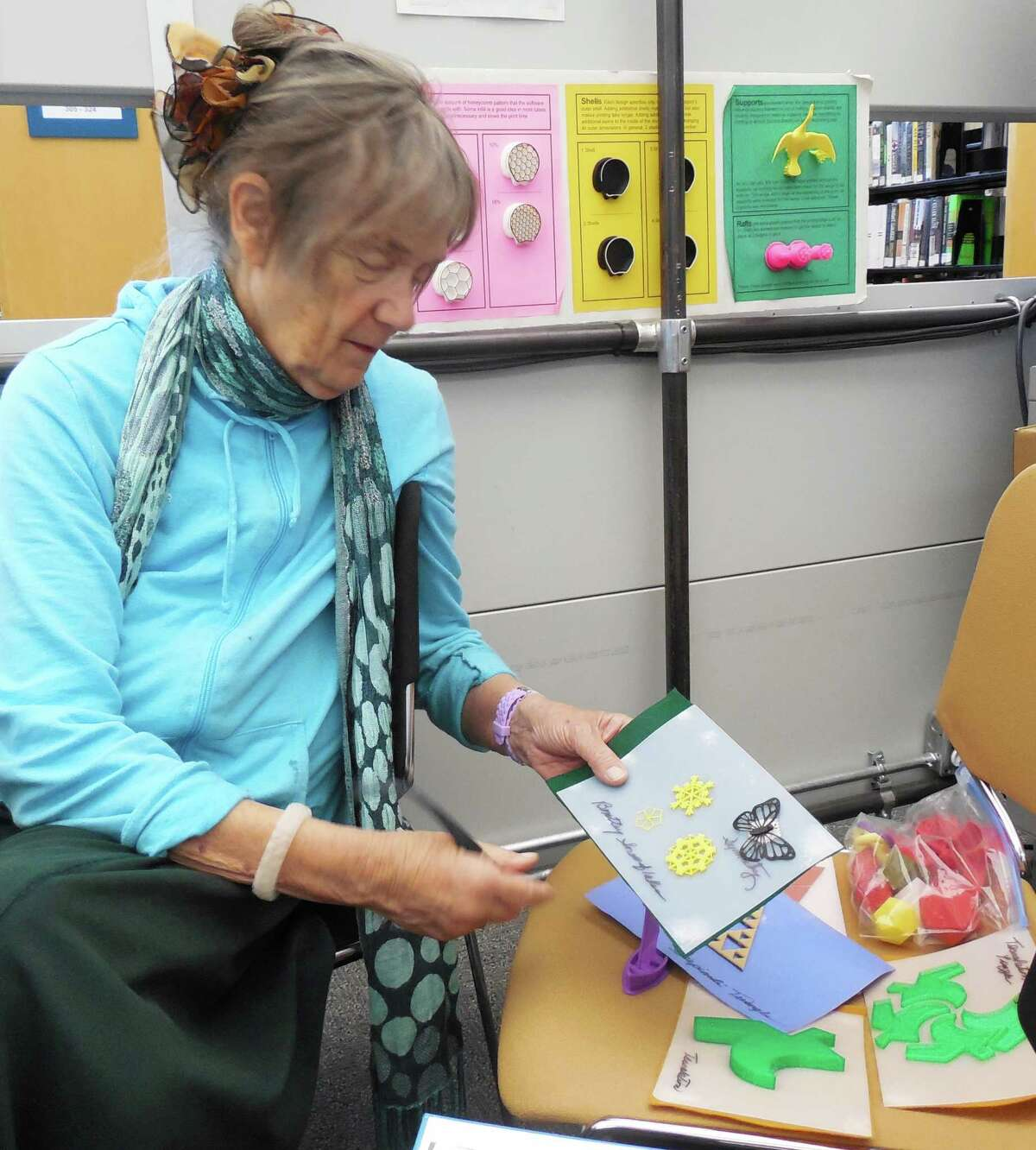 Micki McCabe shows some of the items she's made using the 3D printer at the Westport Library. McCabe, an educational consultant with the Connecticut Braille Association, Inc., is putting the 3D characters into picture books for young blind children.