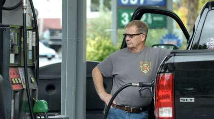 Bud Koral, of New Fairfield, pumps gas into his truck at the Friendly Service Station, on Main Street, in Danbury, Conn, on Wednesday, October 15, 2014. With gas prices in Connecticut the lowest they have been since 2011 analysts are predicting we could see gasoline below $3.00 a gallon.