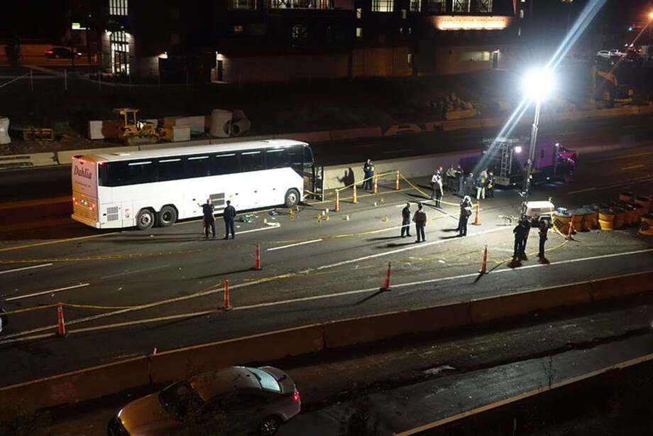 Law enforcement investigate the scene of a stabbing aboard a tour bus late Tuesday, Oct. 14, 2014 in Norwalk, Conn.   A man who stabbed passengers on the casino-bound tour bus on Interstate 95 was fatally shot by state police, officials said Wednesday. The unidentified man began attacking passengers around 10 p.m., state police spokesman Lt. Paul Vance said. The bus driver flagged down a trooper at a construction site. The suspect acted aggressively toward the trooper and was shot when he refused to drop his weapon. Photo: Jeff Dale, Jeff Dale/The Hour / Associated Press AP Photo/The Hour, Jeff Dale