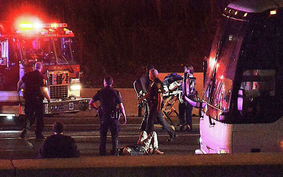 Law enforcement investigate the scene of a stabbing aboard a tour bus late Tuesday, Oct. 14, 2014 in Norwalk, Conn.   A man who stabbed passengers on the casino-bound tour bus on Interstate 95 was fatally shot by state police, officials said Wednesday. The unidentified man began attacking passengers around 10 p.m., state police spokesman Lt. Paul Vance said. The bus driver flagged down a trooper at a construction site. The suspect acted aggressively toward the trooper and was shot when he refused to drop his weapon. Photo: Contributed Photo, Harold Cobin/Contributed Photo / Connecticut Post Contributed Harold Cobin