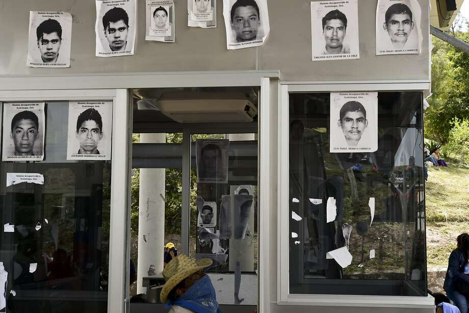 Pictures of missing students were stuck on one of the tollbooths across the Chilpancingo-Acapulco highway, which were taken over by teachers and students during a protest  on October 15, 2014 in Chilpancingo, Guerrero state, Mexico. The mystery over the fate of 43 Mexican students missing since an attack by gang-linked police deepened after authorities said none was among 28 bodies found in a mass grave.    AFP PHOTO/ Yuri CORTEZYURI CORTEZ/AFP/Getty Images Photo: Yuri Cortez, AFP/Getty Images