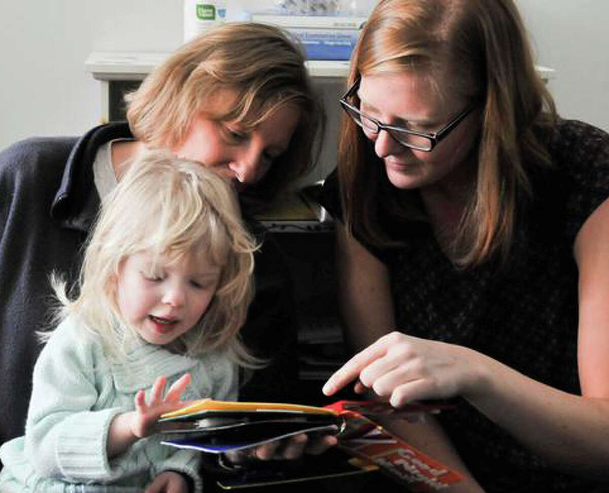 Graduate student Abigale Stangl (right), a Colorado University-Boulder doctoral student and a volunteer at the Anchor Center for Blind Children in Denver, shows Isabella Chinkes and her mother, Linda, a 3D version of