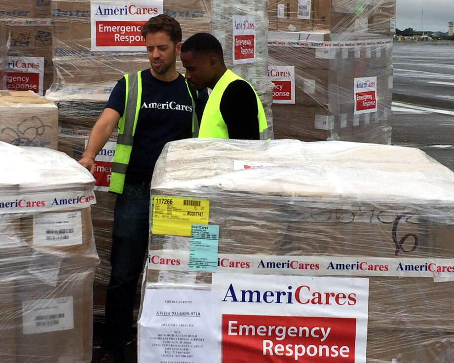 Brian Hoyer, left, escorts a delivery of medicines and personal protective equipment that arrived in Monrovia, Liberia in West Africa on Sept. 29. Photo: Contributed Photo / Stamford Advocate Contributed