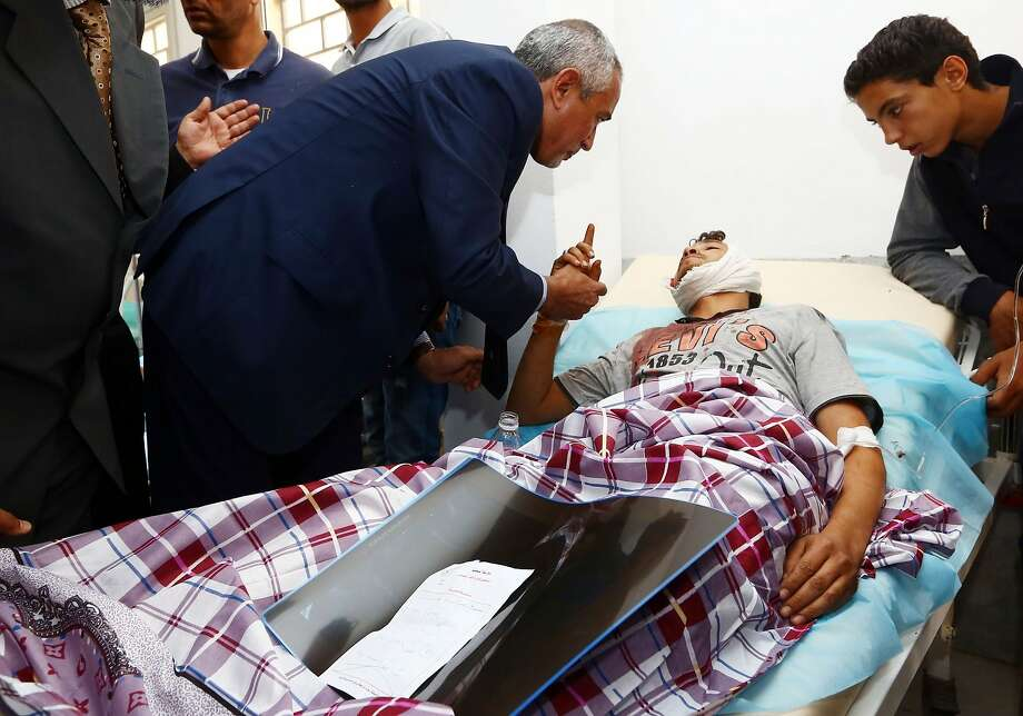 Libyan self-proclaimed pro-Islamist prime minister Omar al-Hassi (C) visits fighters wounded in clashes west of Tripoli between rival tribes, at a hospital in Gharyan, 85 kilometres south of the capital, on October 15, 2014. Clashes between rival militias in Libya have driven an estimated 287,000 people from their homes, including about 100,000 who have fled the outskirts of the capital, according to the UN refugee agency. AFP PHOTO / MAHMUD TURKIAMAHMUD TURKIA/AFP/Getty Images Photo: Mahmud Turkia, AFP/Getty Images