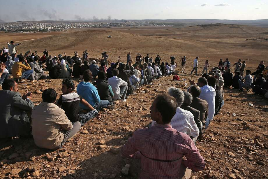 Kurdish people sit in formation to form the initials of the People's Protection Units, or YPG, the main Kurdish militia in Syria, on a hilltop on the outskirts of Suruc, at the Turkey-Syria border, overlooking Kobani, Syria, background, just over the border, in support of Syrian Kurds fighting the militants of Islamic State group, Wednesday, Oct. 15, 2014. Kobani, also known as Ayn Arab, and its surrounding areas, has been under assault by extremists of the Islamic State group since mid-September and is being defended by Kurdish fighters. (AP Photo/Lefteris Pitarakis) Photo: Lefteris Pitarakis, Associated Press