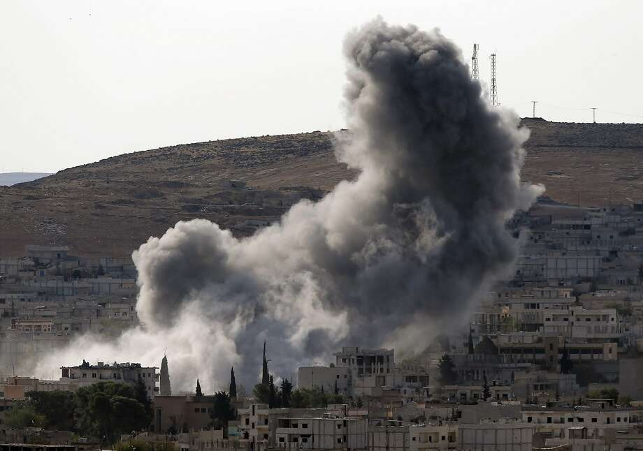 Thick smoke rises following an airstrike by the US-led coalition in Kobani, Syria while fighting continued between Syrian Kurds and the militants of Islamic State group, as seen from Mursitpinar on the outskirts of Suruc, at the Turkey-Syria border, Wednesday, Oct. 15, 2014. Kobani, also known as Ayn Arab, and its surrounding areas, has been under assault by extremists of the Islamic State group since mid-September and is being defended by Kurdish fighters. (AP Photo/Lefteris Pitarakis) Photo: Lefteris Pitarakis, Associated Press