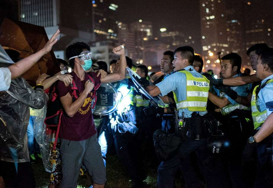 TOPSHOTS A pro-democracy protester (2L) shakes his fist at police officers as they advance in Hong Kong on October 15, 2014. Hong Kong has been plunged into the worst political crisis since its 1997 handover as pro-democracy activists take over the streets following China's refusal to grant citizens full universal suffrage.  AFP PHOTO / ALEX OGLEAlex Ogle/AFP/Getty Images Photo: Alex Ogle, AFP/Getty Images