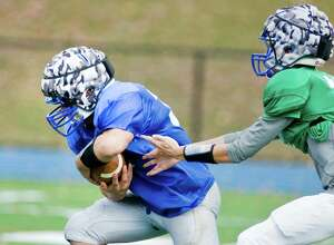 Nick Rubino takes the handoff during a Newtown High School football practice. Wednesday, Oct. 15, 2014