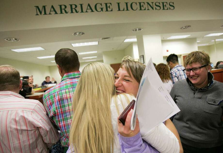 Amber Beierle, center right, gets a hug from Mistie Tolman after she and partner Rachael Beierle, right, received their marriage license Wednesday morning, OCt. 15, 2014, at the Ada County Courthouse Recorder's office in Boise, Idaho. Amber and Rachael were part of four couples who sued the state over Idaho's ban on same-sex marriage. (AP Photo/The Idaho Statesman, Kyle Green)  LOCAL TELEVISION OUT (KTVB 7); MANDATORY CREDIT Photo: Kyle Green / Associated Press / The Idaho Statesman