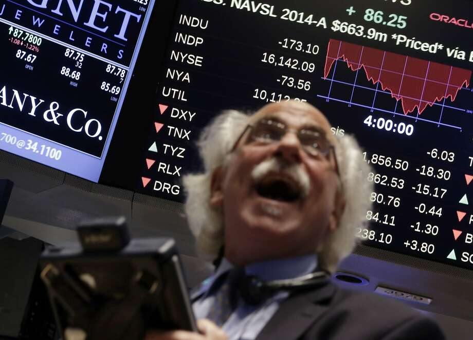 Trader Peter Tuchman watches a screen above the floor of the floor of the New York Stock Exchange at the closing bell, Wednesday, Oct. 15, 2014. The Dow Jones industrial average plummeted as much as 460 points in afternoon trading, then clawed back much of the ground it lost. It ended down 173 points, or 1.1 percent. (AP Photo/Richard Drew) Photo: Richard Drew, Associated Press