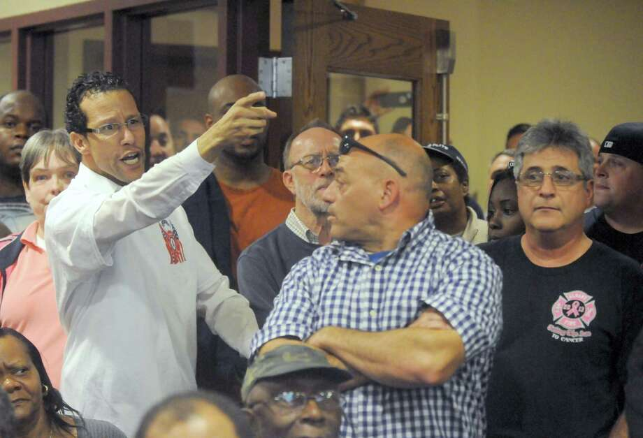 Andres Rivera,left, wearing a save Ladder 1 shirt dets involved in the shouting over Ladder 1 during Mayor Kathy Sheehana€™s town hall meeting on the city budget  Wednesday Oct. 15, 2014 in Albany, N.Y.  (Michael P. Farrell/Times Union) Photo: Michael P. Farrell / 00029045A
