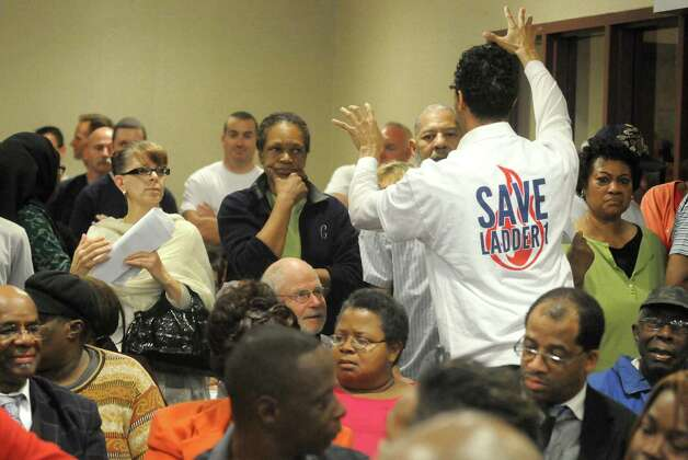 Andres Rivera, right, wearing a save Ladder 1 shirt trys to calm the crowd during Mayor Kathy Sheehana€™s town hall meeting on the city budget  Wednesday Oct. 15, 2014 in Albany, N.Y.  (Michael P. Farrell/Times Union) Photo: Michael P. Farrell / 00029045A
